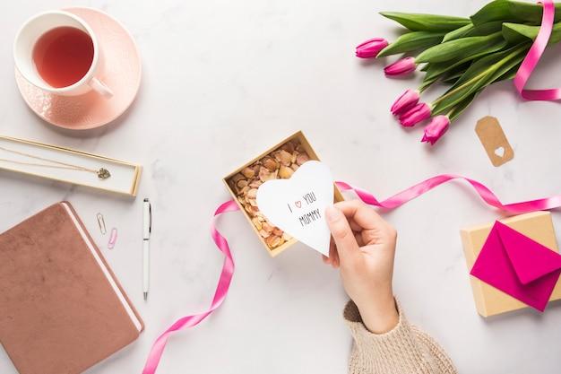 Mão segurando o coração de papel de dia das mães