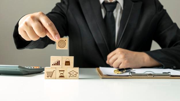 Mão segurando o cubo de madeira com objetivos e metas virtuais, objetivos de sucesso de negócios, objetivos, ideias financeiras e de crescimento de negócios.