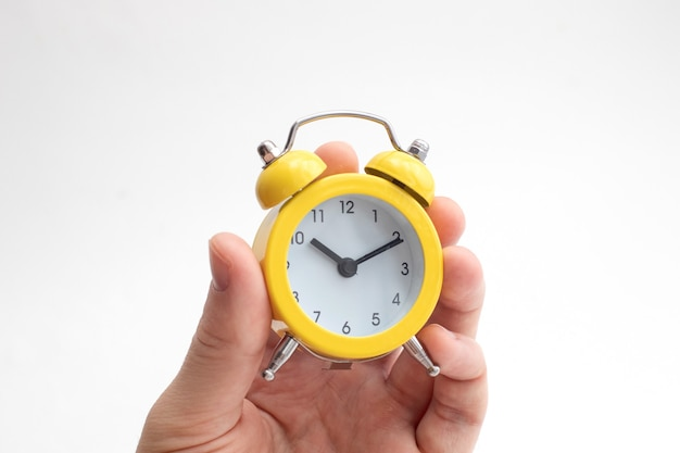 Mão segurando o despertador amarelo sobre fundo claro. conceito de tempo. mantenha seu tempo.