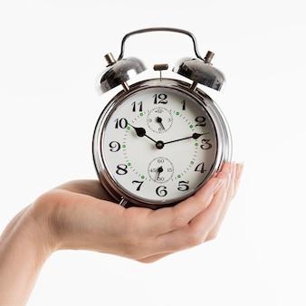 Mão segurando o despertador