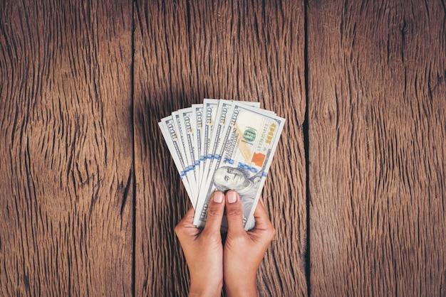 Mão segurando o dinheiro de notas de dólar em fundo de madeira