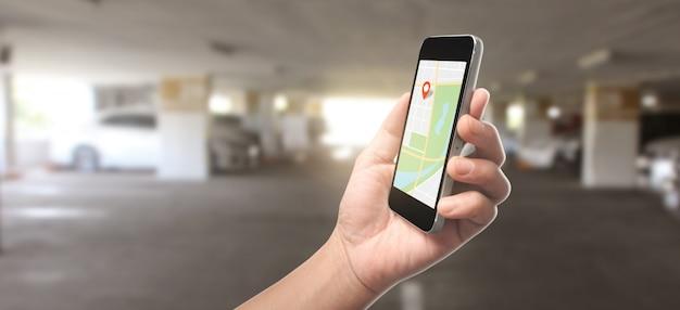Mão segurando o dispositivo smartphone e tela tocante, que é um ícone vermelho da localização, conceito de navegação on-line