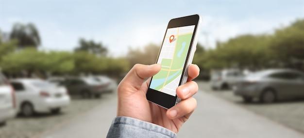 Mão segurando o dispositivo smartphone tocando a tela e o mapa gps do navegador