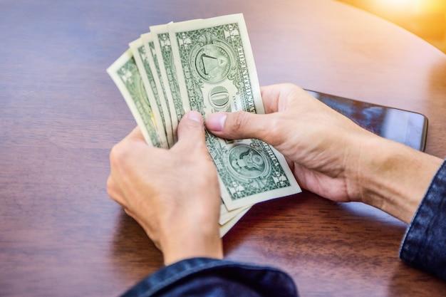 Mão segurando o dólar para fazer compras, economia de notas de dinheiro e conceito de investimento