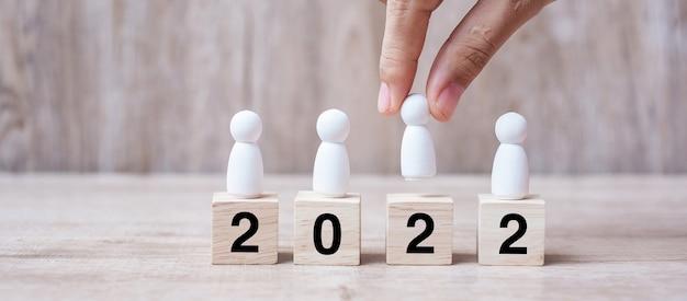 Mão segurando o empresário sobre o edifício de blocos com texto de 2022. liderança, negócios, equipe, trabalho em equipe e conceito de resolução de ano novo