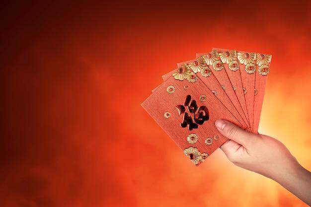 Mão segurando o envelope vermelho chinês