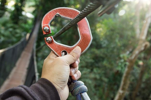 Mão segurando o equipamento de tirolesa na árvore andando, aventura