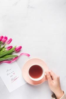 Mão segurando o espaço de cópia de caneca de chá