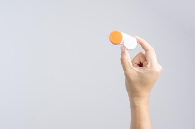 Mão segurando o estojo de lentes de contato