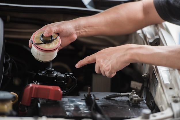 Mão segurando o filtro de combustível e aponte para o motor automotivo