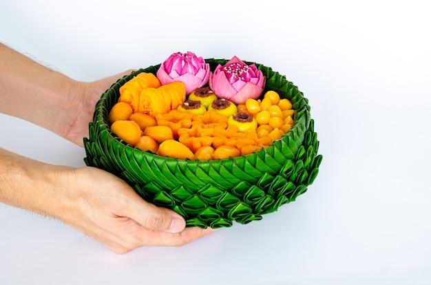 Mão segurando o foco parcial de sobremesas de casamento tailandês em um prato de folhas de bananeira ou krathong para cerimônia tradicional tailandesa
