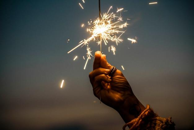 Mão segurando o fogo de artifício do estrelinha com o céu do pôr do sol no fundo