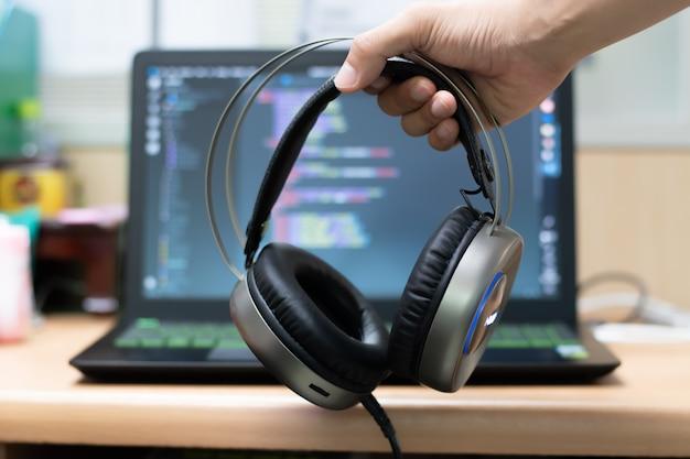 Mão segurando o fone de ouvido no fundo do laptop.