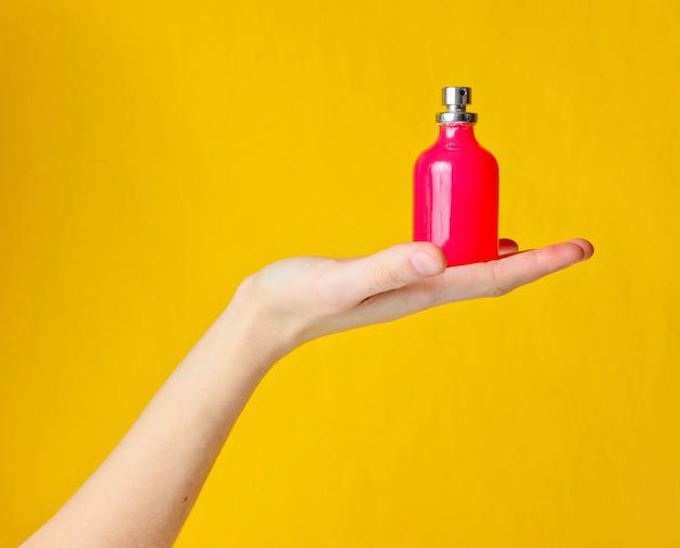 Mão segurando o frasco de perfume