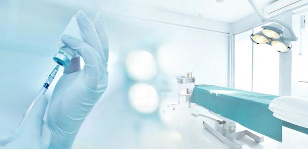 Mão segurando o frasco de seringa e medicamento preparar para injeção na sala de cirurgia com tom azul