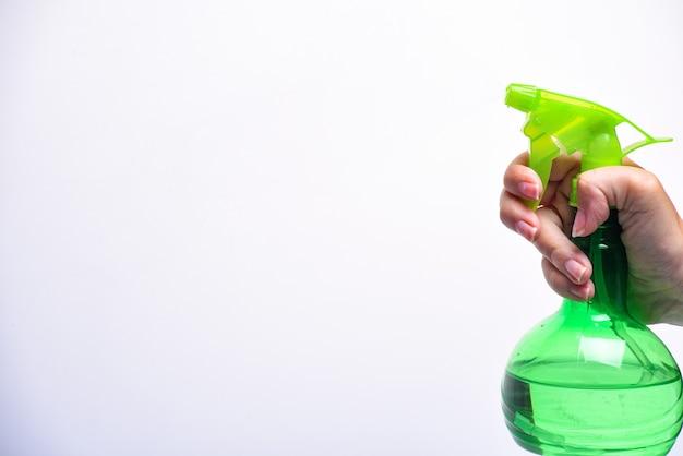 Mão segurando o frasco de spray de plástico verde - segure o frasco de spray de plástico isolado no branco. homem com pulverizador de água na mão. copie o espaço
