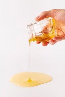 Mão segurando o frasco derramando mel