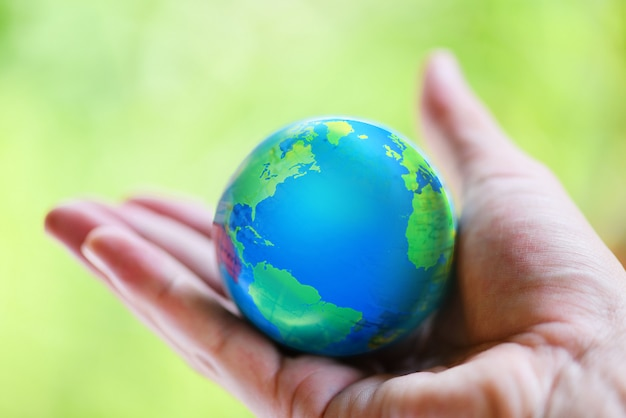 Mão segurando o globo com mapa e ambiente verde planeta salvar a terra
