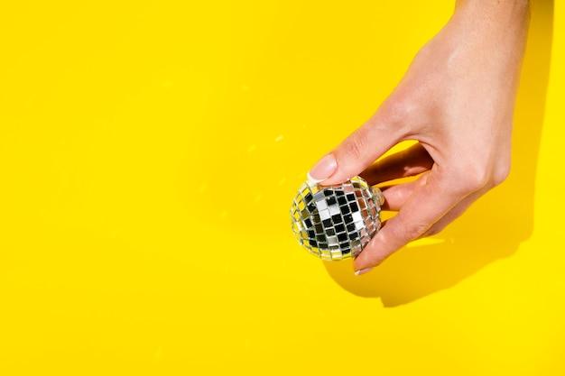 Mão segurando o globo discoteca com espaço de cópia