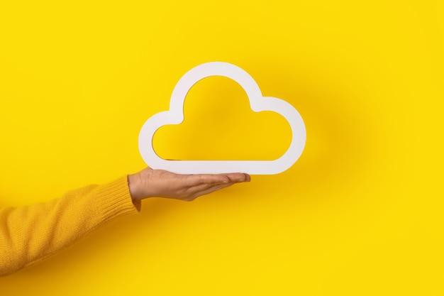 Mão segurando o ícone da nuvem sobre fundo amarelo