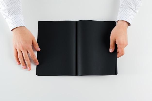 Mão segurando o livro aberto em branco simulado