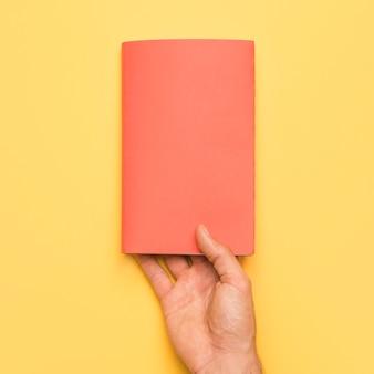 Mão segurando o livro com capa vermelha