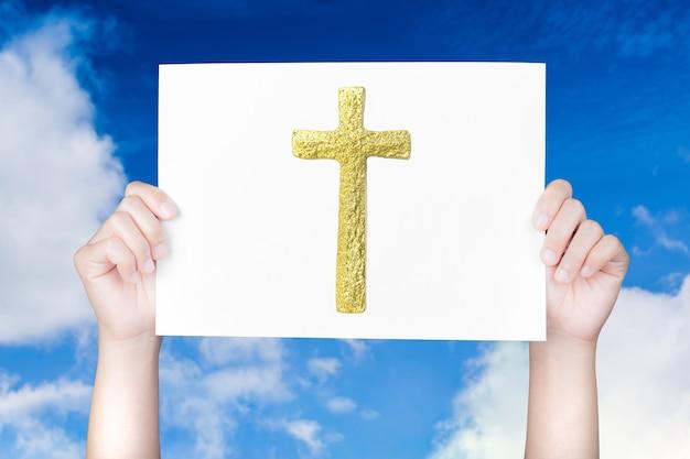 Mão segurando o livro da bíblia no fundo do céu azul
