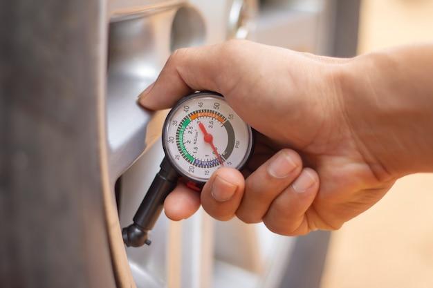 Mão segurando o manômetro para medição de pressão de pneu de carro