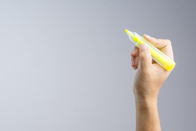 Mão segurando o marcador amarelo para escrever um marcador de palavra de cor