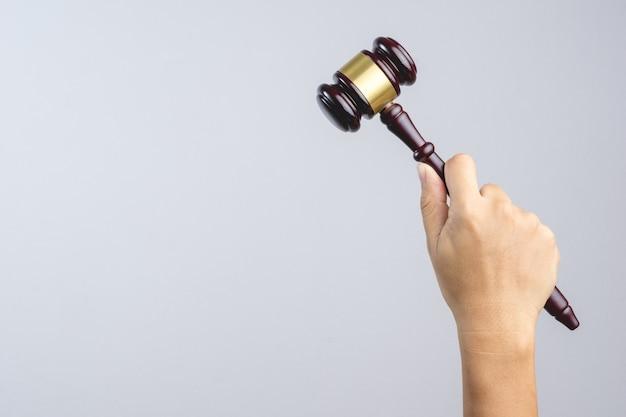 Mão segurando o martelo do juiz de madeira como um sinal de lei ou justiça