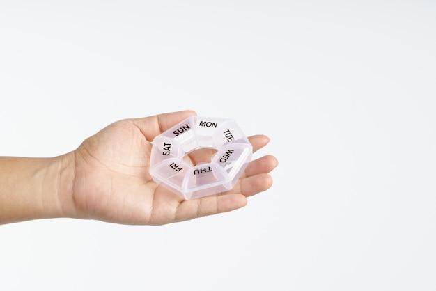 Mão segurando o medicamento comprimidos recipiente de caixa plástica