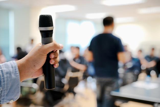 Mão segurando o microfone em pé no palco e relatórios para o público