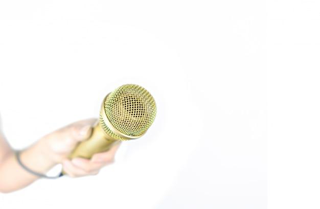 Mão segurando o microfone ouro isolado