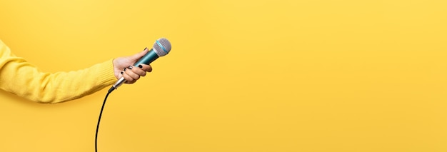 Mão segurando o microfone sobre fundo amarelo, imagem panorâmica simulada