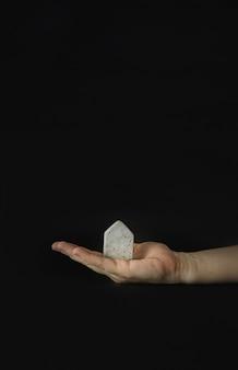 Mão segurando o modelo de mini casa no fundo preto. compre ou construa uma casa. conceito de escada de propriedade, hipoteca e investimento imobiliário. espaço livre para texto, cópia espaço, layout moderno.