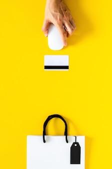 Mão segurando o mouse sem fio para compras online com cartão de crédito em fundo amarelo. conceito de cyber monday e black friday.