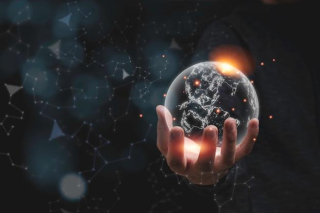 Mão segurando o mundo virtual com luz laranja. conceito de conservação do meio ambiente.