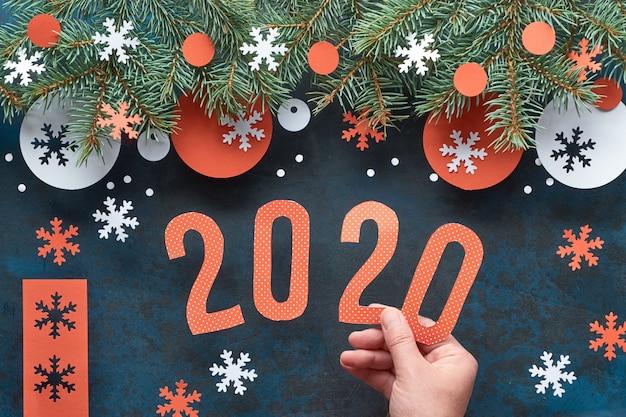 Mão segurando o número 2020, fundo de natal com galhos de pinheiro, decorações de papel vermelho e branco