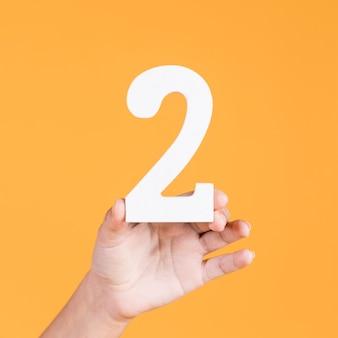 Mão segurando o número dois sobre fundo amarelo