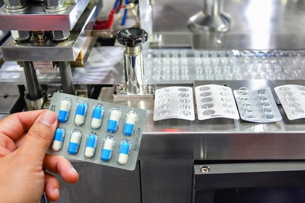 Mão segurando o pacote de cápsulas azuis na linha de produção de pílulas medicinais industrial