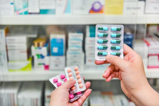 Mão segurando o pacote de cápsulas de remédio na farmácia