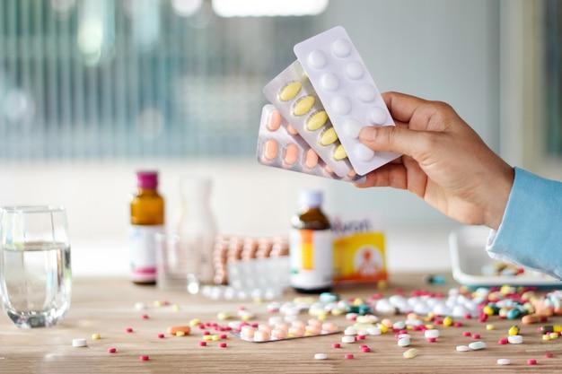 Mão segurando o pacote de medicamentos pílula com medicamentos coloridos espalhados
