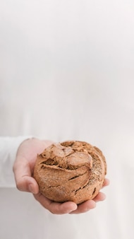 Mão segurando o pão com fundo branco