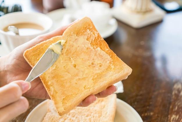 Mão segurando o pão e manteiga para o café da manhã