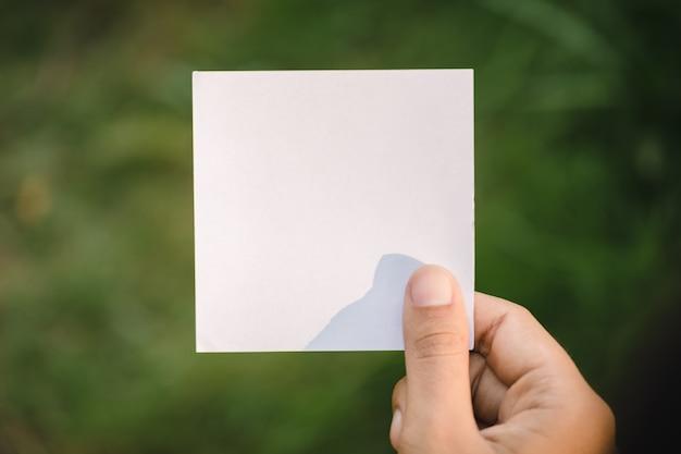 Mão segurando o papel em branco na natureza