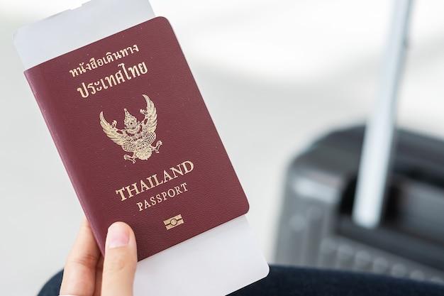 Mão segurando o passaporte da tailândia e o bilhete do cartão de embarque com saco de bagagem.