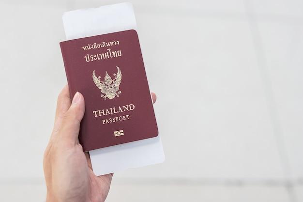 Mão segurando o passaporte da tailândia e o bilhete do cartão de embarque.