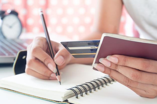 Mão segurando o passaporte e cartão de crédito. conceito de viagem, seguro ou pagamento eletrônico