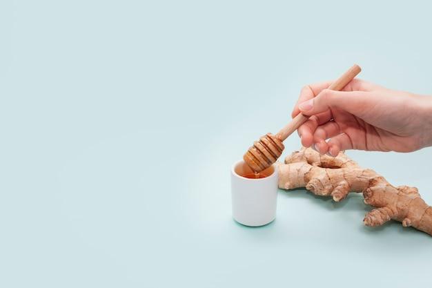 Mão segurando o pau de mel com espaço de cópia