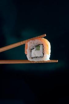 Mão segurando o pauzinho para comer sushi